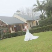 Bride on grass in front of chapel