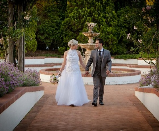 Bride and groom walking along path