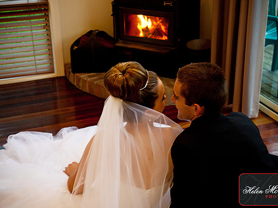 Bride and groom before fireplace